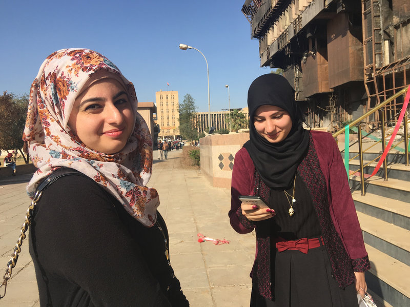 Sisters Raffal, left, and Farah Khaled are first-year students at Mosul University in Iraq. They're standing outside the university library, which was burned down, along with most of its books, by ISIS when it controlled the city. Jane Arraf/NPR